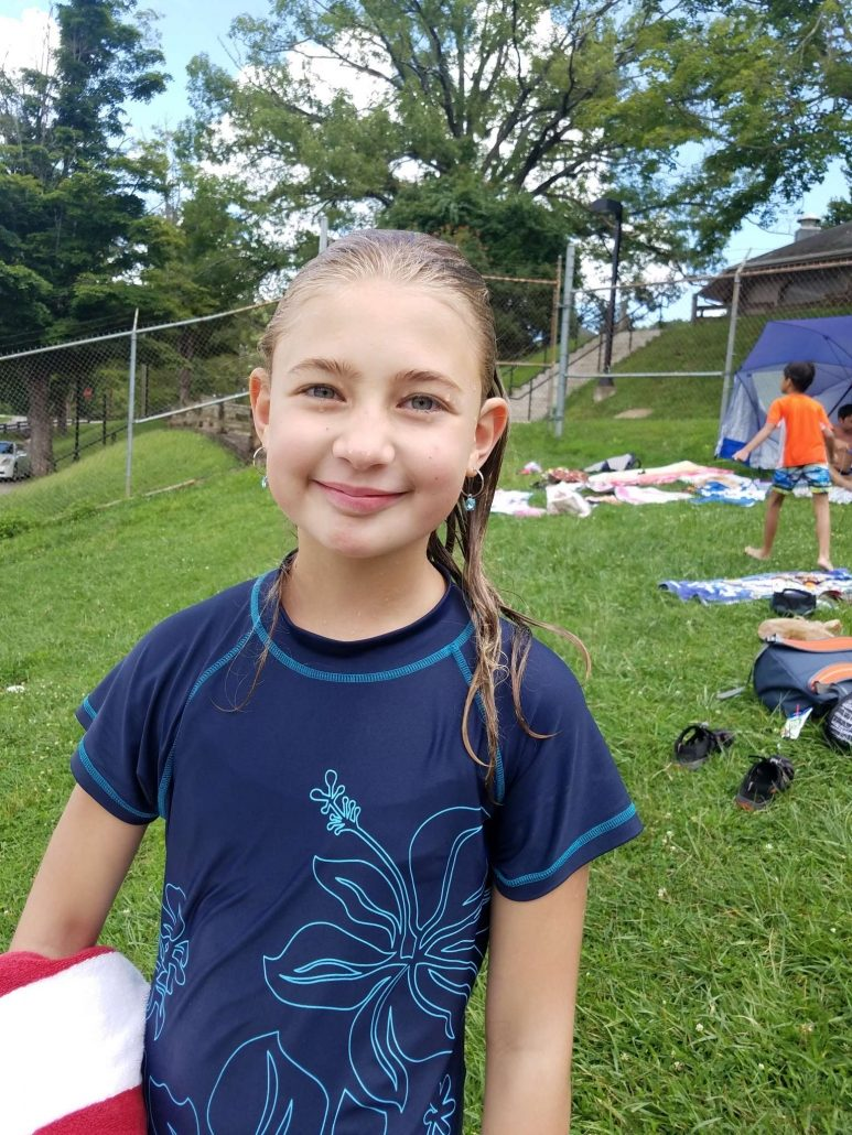 Young girl smiling while attending summer camp