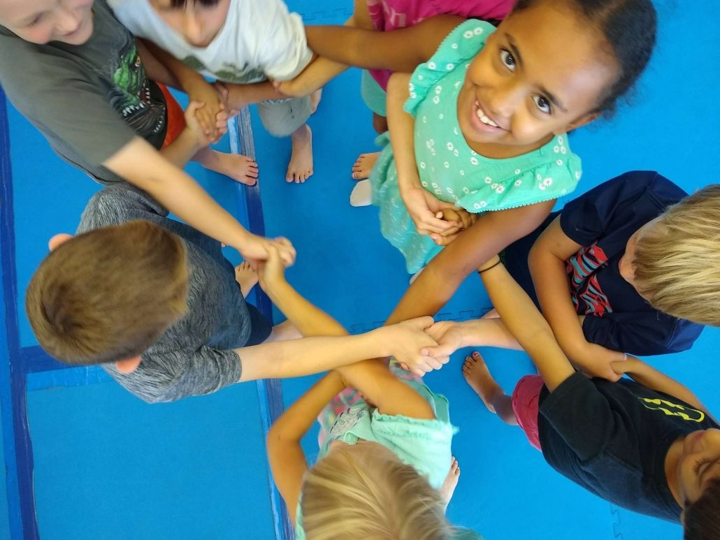 Several children holding hands during taekwondo summer camp