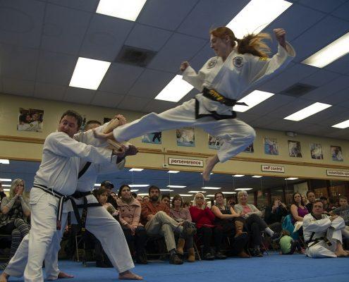 photo of teen girl breaking a board using a flying sidekick