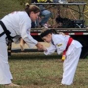 Photo of woman with a 2nd degree black belt shaking the hand of a girl who has just broken a board
