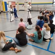 Photo of Grandmaster Morris and Master Amy Dexter with elementary aged student practitioner