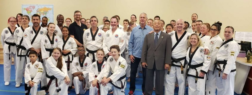Photo of TKD students in the Black Belt ranks with 3 Grandmaster instructors