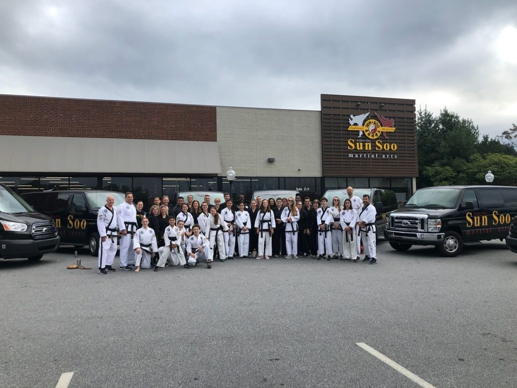 Photo of Black Belt students and Asheville Sun Soo vans in front of the dojang
