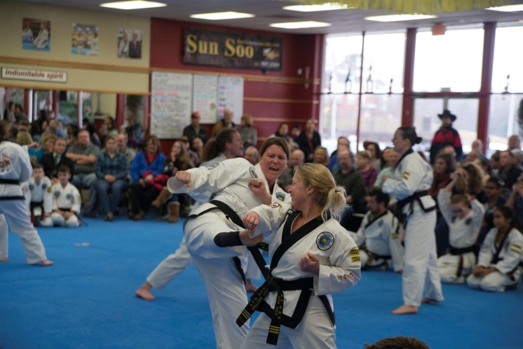 Adult women practice taekwondo sparring techniques